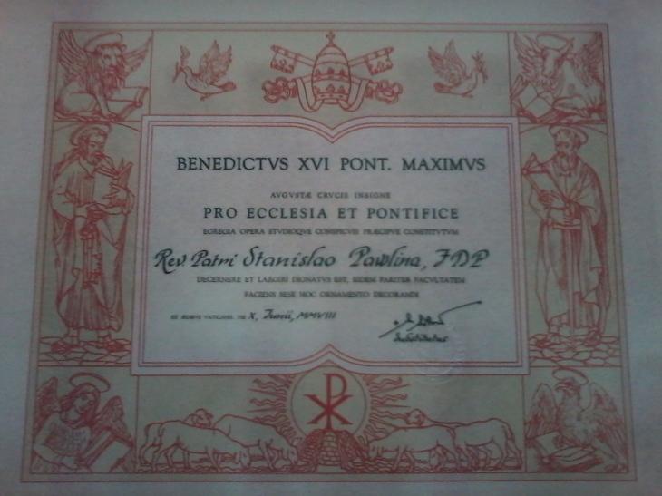 Dokument potwierdzający przyznanie Krzyża Zasługi Dla Kościoła i Papieża od Jego Świątobliwość papieża Benedykta XVI. Podpisany przez Jego Eminencję kardynała Tarcisio Bertone, przyznany w dowód uznania za pracę na rzecz Kościoła w dniu 10 czerwca 2008 r.