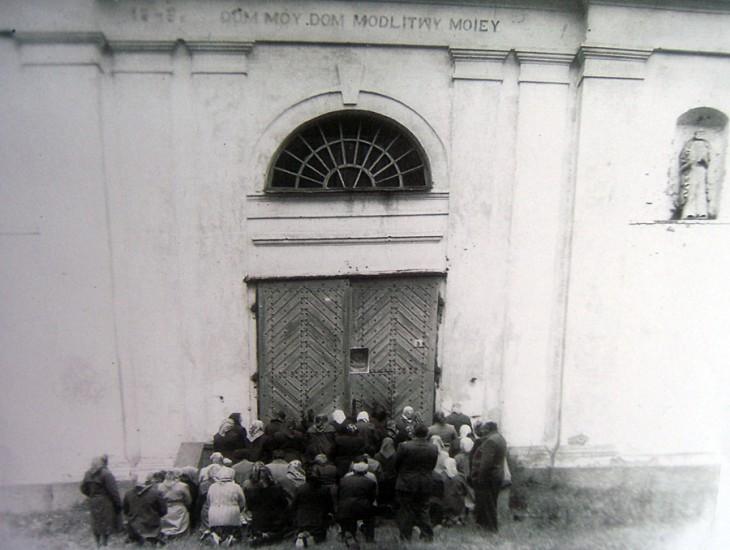 Wierni, modlące się przy zamkniętych drzwiach kościoła w Szereszewie. Lata 60.-te XX w.